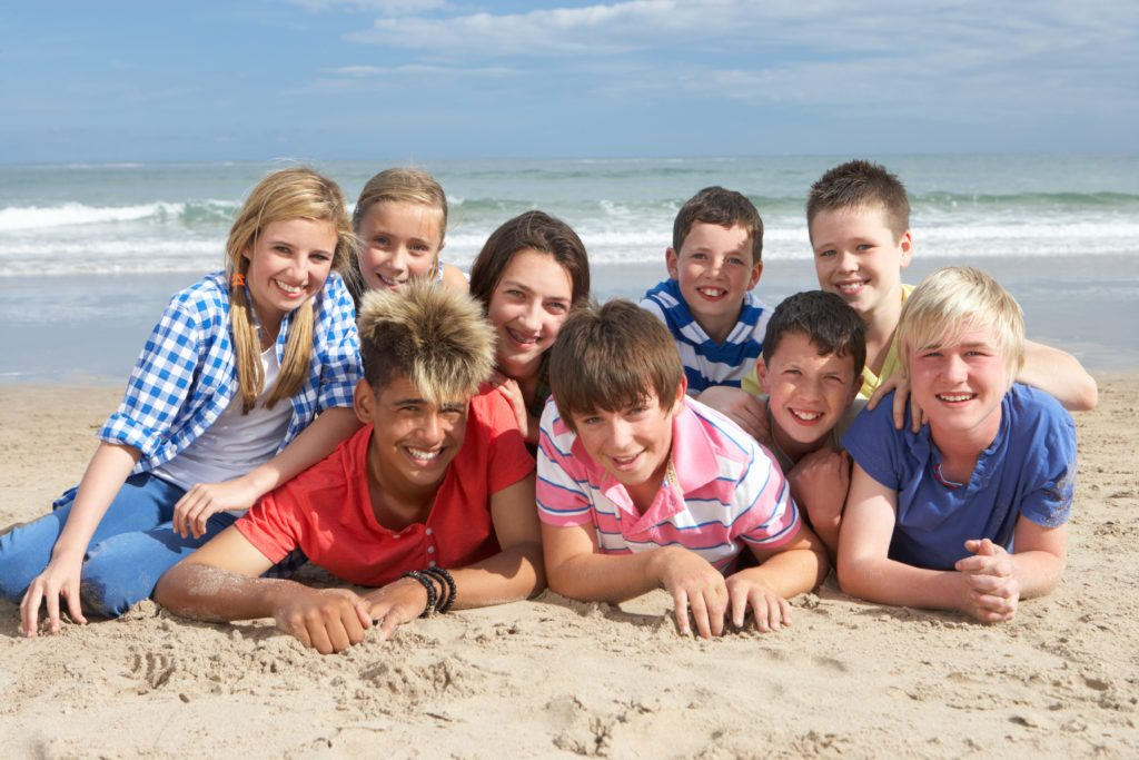 Young people posing on a beach.